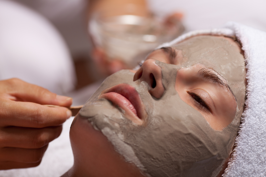 Beautician applying a clay mask on beautiful face of young girl