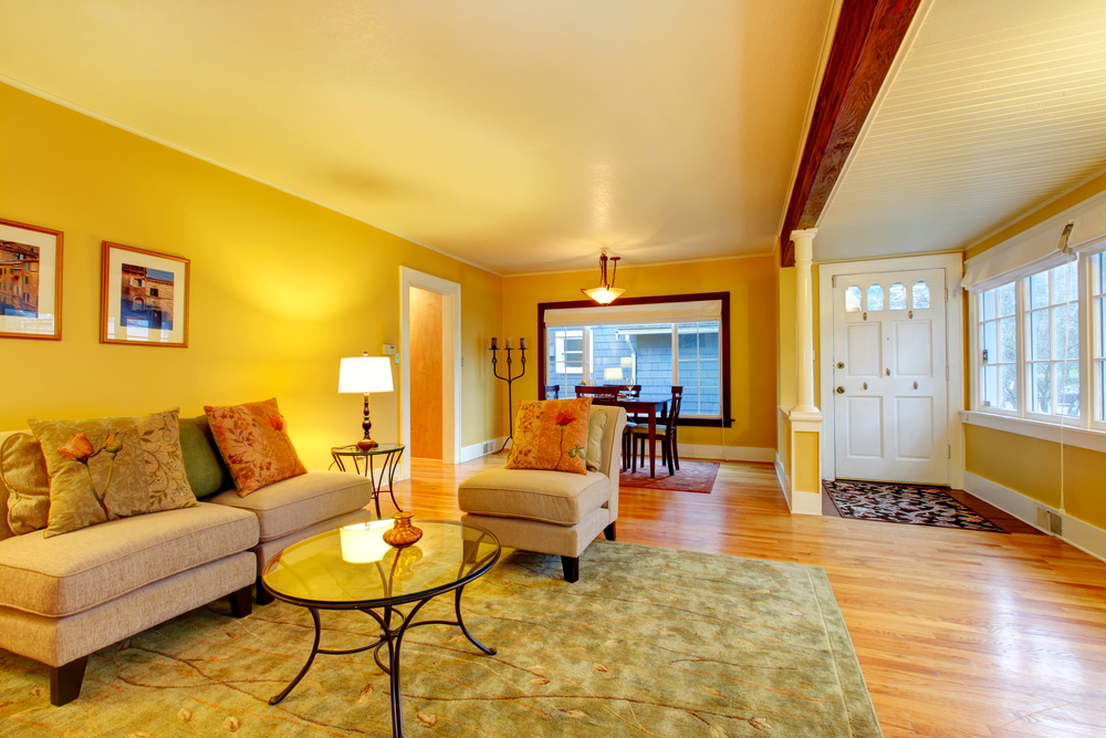 Image of a yellow colored living room with the main entrance in the background.